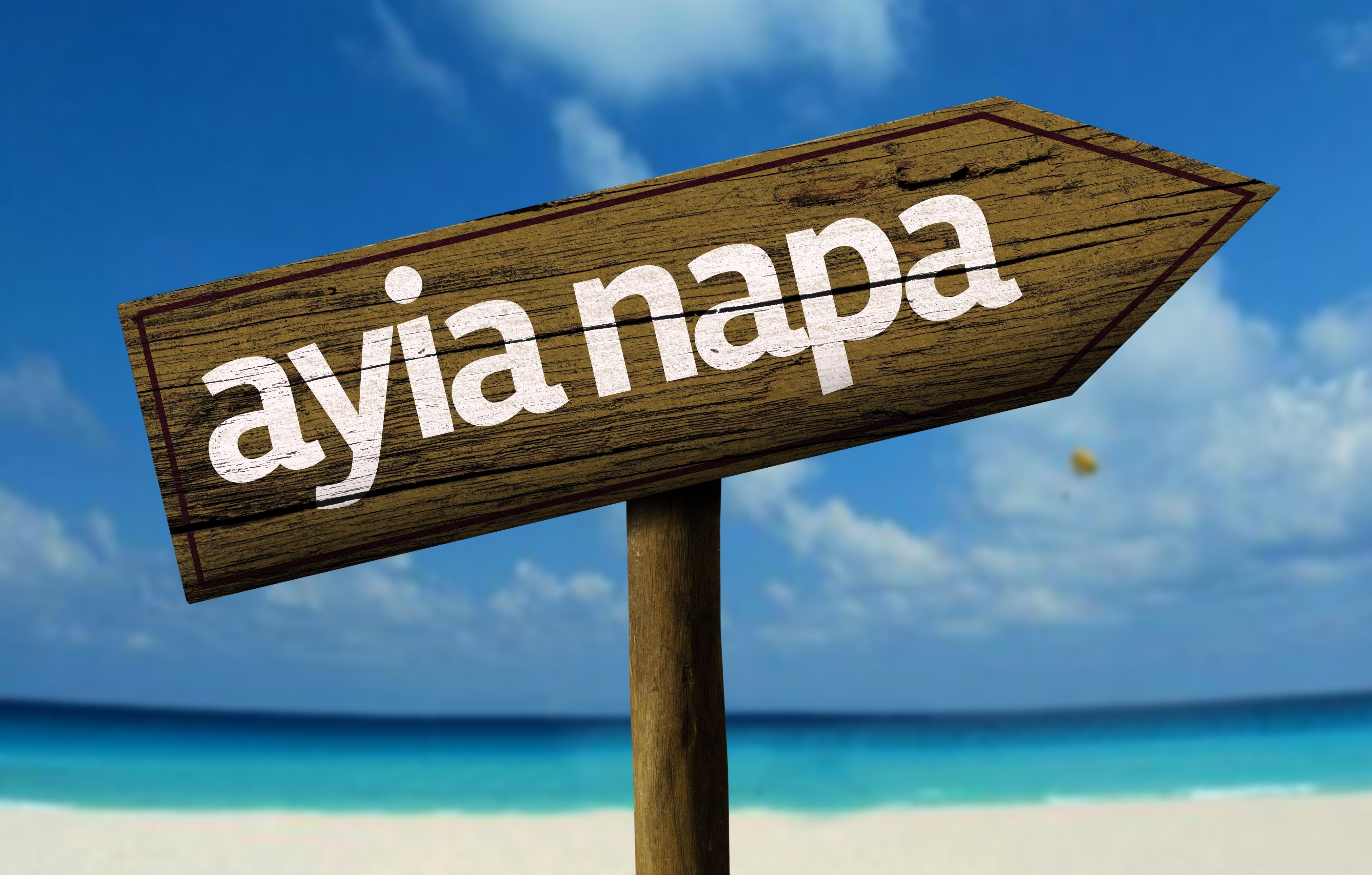 Big ayia napa wooden sign with a beach on background